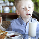 child at table drinking milk at restaurant