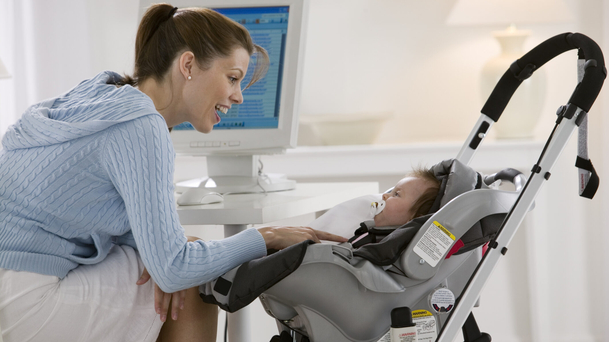 Mom with baby in a car seat carrier stroller frame.