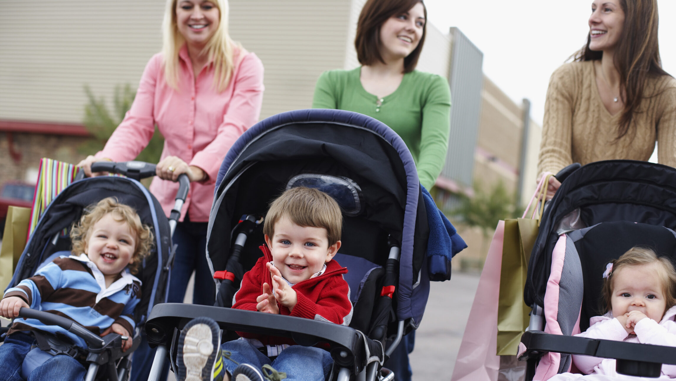 Moms walking in the city with babies in strollers.